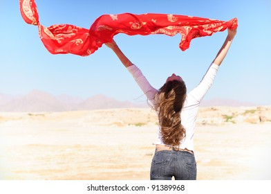 woman in desert with red shawl