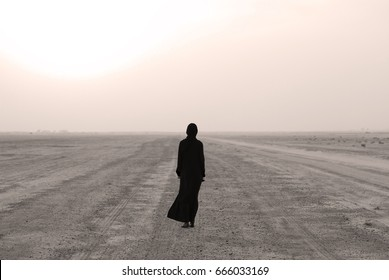 Woman in the desert wearing arabic dress
