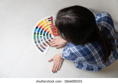 A woman designer choosing an interior colour using the color palette, while sitting on the floor. Blurred background.