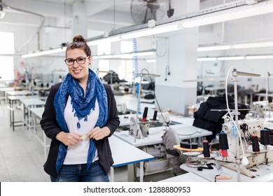 Woman designer posing in textile factory.