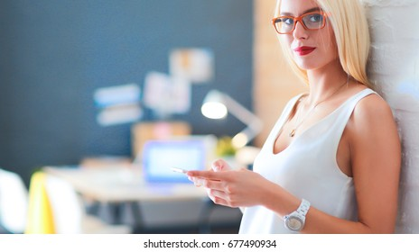 Woman designer using on mobile phone in office