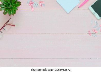 Woman desk with pink pen, paper, coffee cup, glasses and succulent. Top view flat lay overhead. Copy space background