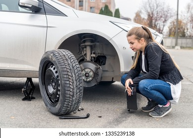 Woman in despair looking at spare wheel for car