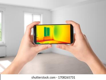 Woman detecting heat loss in room using thermal viewer on smartphone. Energy efficiency