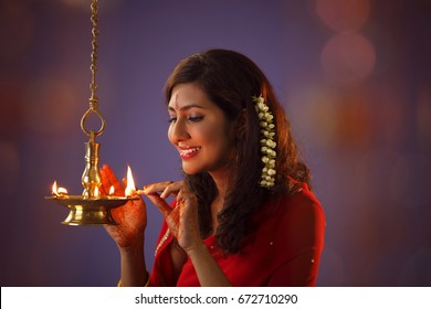 woman devotee lights  lamps as she celebrate 'deepavali'