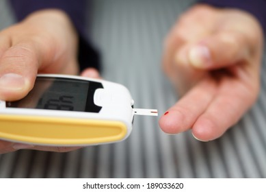 Woman with diabetes doing a blood test with a glucometer