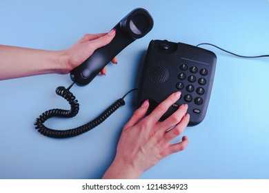 Woman dialing a number on old fashioned phone