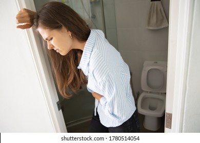 woman with diarrhea; sick woman suffering from diarrhea, stomachache, menstrual period cramp, abdominal pain, food poisoning, gastritis, constipation; caucasian young adult woman health care model