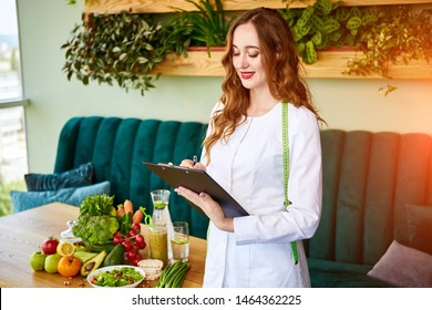 Woman dietitian in medical uniform with tape measure working on a diet plan standing with different healthy food ingredients in the green office on background. Weight loss and right nutrition concept