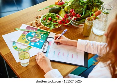Woman dietitian in medical uniform with tape measure working on a diet plan sitting with different healthy food ingredients in the green office on background. Weight loss and right nutrition concept - Shutterstock ID 1515243626