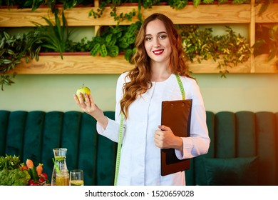 Woman dietitian in medical uniform with tape measure holds apple standing with different healthy food ingredients in the green office on background. Weight loss and right nutrition concept