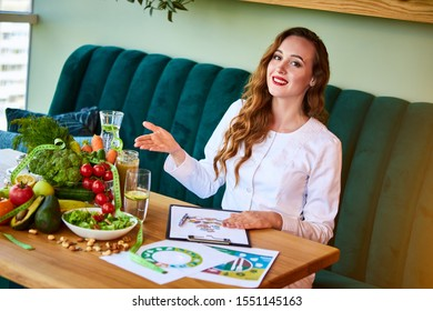 Woman dietitian in medical uniform with tape measure working on a diet plan sitting with different healthy food ingredients in the green office. Weight loss and right nutrition concept