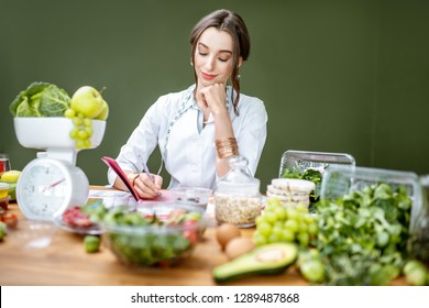 Woman dietitian in medical uniform working on a diet plan sitting with various healthy food ingredients in the green office