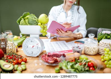 Woman dietitian working on a diet plan sitting with various healthy food ingredients, cropped image focused on food