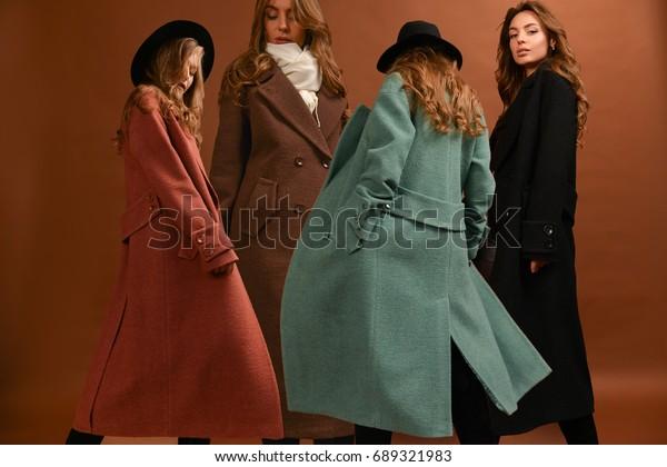 黒い背景に色とりどりの長いコートを着た女性。茶色の、暗い赤、緑の、スカーフと黒い帽子、茶色の背景に波状の髪を動かして