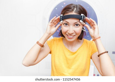 Woman with digital headwear equipment sensor connected to her ear, reading brain impulses. Future technology concept