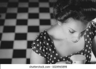 Woman in diner with tea cup looking down at floor vintage 1950's inspired black and white retro