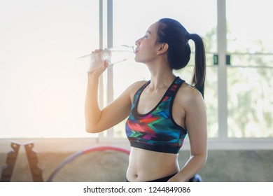 Woman dink up water bottle after fitness at the gym