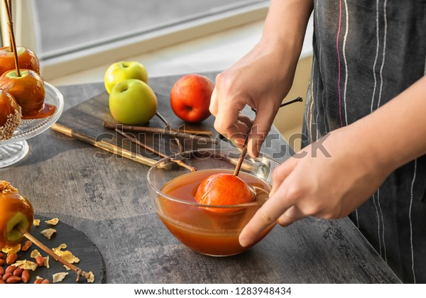 Woman dipping apple into glass bowl with caramel at grey table