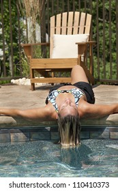 Woman dipping her hair in swimming pool.