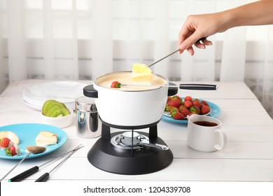 Woman dipping pineapple into pot with white chocolate fondue on table
