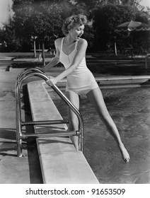 Woman dipping toes in outdoor swimming pool