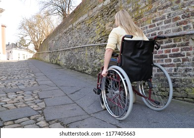 Woman with disability in a wheelchair goes up a long steep slope