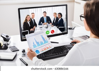 Woman Discussing Graph With Her Colleagues On Video Conference On Computer At Workplace
