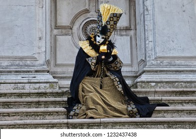 Woman disguised in beautiful black dress with glittering elements is sitting on the stairs and posing in front of historic building in Venice, Italy during the traditional Carnival. Photo: Feb 2013