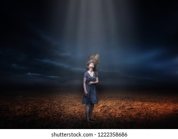 Woman with disheveled hair standing on field in lightbeam under dark storm sky. Surreal photography.