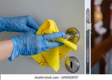 The woman is disinfecting the door handle to prevent infectious disease