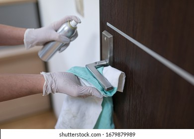 The woman disinfects the door handle with a disinfectant liquid.