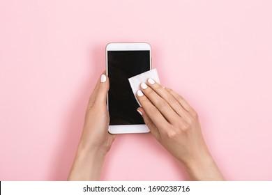 女性がスマートフォンの画面を消毒する。細菌や汚れから身を守れ。ガジェットを清潔に保つ。