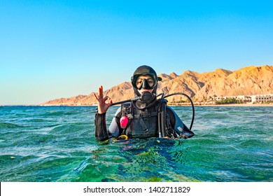 Woman diver floated on the surface of the sea and shows a hand sign that all is well. Red Sea, Egypt.