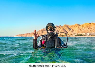 Der Tauchertaucher flog auf der Meeresoberfläche und zeigt ein Handzeichen, dass alles gut ist. Rotes Meer, Ägypten.