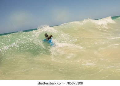 A woman dives into a big wave at Swanbourne Beach in Perth, Western Australia.