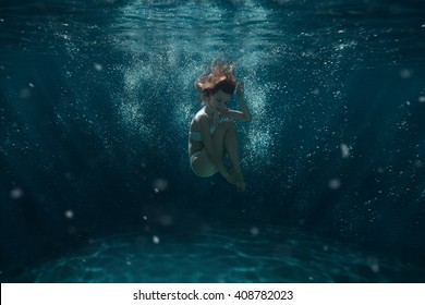 Woman dives under water among the rays of light and air bubbles.