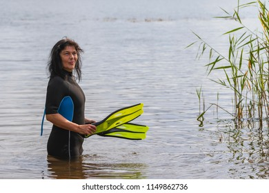 Woman with diving fins and wetsuit