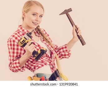 Woman with DIY toolbelt holding drill and hammer. Girl working at flat remodeling. Building, repair and renovation.