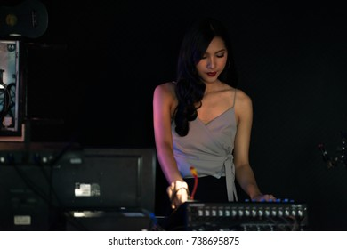 Woman DJ party concept. Young Chinese woman DJ mixing music on colorful background listening to her music. Selective focus with blurred background.