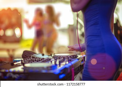 woman DJ takes control platter spindle of rhythm music with and mixer dash board, playing the song at the party, adjusting with the controller, fun of music and light colors, Music & Event party