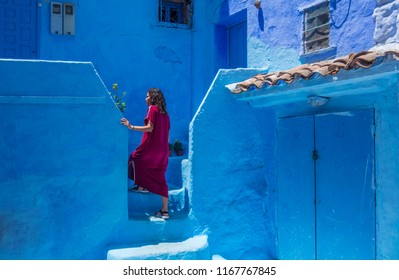 Woman with djellaba in Chefchouen street, famous blue city. Traditional moroccan architectural details