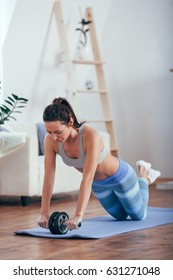 woman with do abdominal exercises with wheel. Workout exercise at home to lose weight