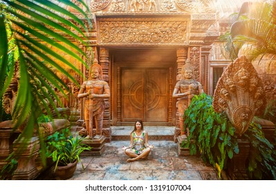 Woman do energy kundalini yoga in lotus pose near temple hindu cambodia on sunset green nature place. Meditation enlightenment concept. Meditating person near trees and old building. Open chakras