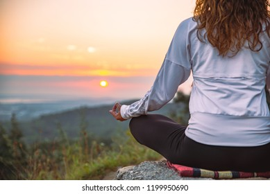 woman do yoga exercises at top of the hill on sunrise. lifestyle concept