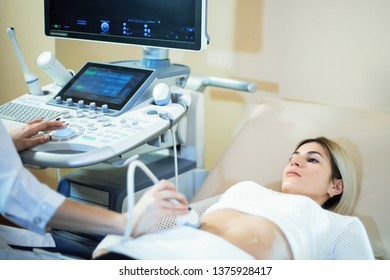 Woman doctor conducts an ultrasound study of the patient.
