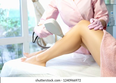 Woman doctor cosmetologist removing hair from a woman client body using laser epilator. They in a spa center