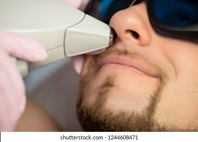 Woman doctor cosmetologist removing hair from a man body using laser epilator. They in a spa center