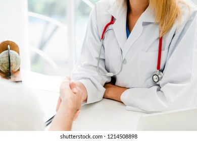 Woman doctor doing handshake with male patient in hospital office room. Healthcare and medical service occupation.