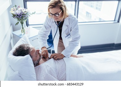 Woman doctor examining heartbeats with stethoscope on a hospitalised man. Physician attending male patient for routine checkup.
